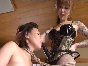 Nasty asian mistress fucks her slave girl rough.