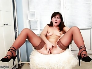 Brunette Dushenka has fire in her eyes as she masturbates