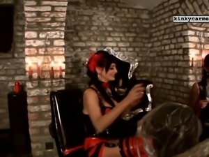 Hot dommes in red and black leather give stud slaves a spanking in a BDSM...