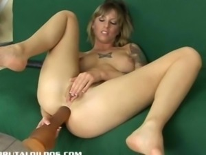 Inked milf Tricia swallowing a thick dildo with her ass